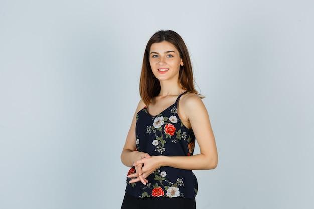Porträt einer attraktiven dame, die die finger in der bluse hält und fröhliche vorderansicht sieht