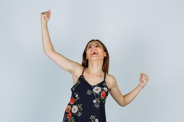 Porträt einer attraktiven dame, die siegergeste in bluse zeigt und glückliche vorderansicht sieht