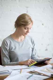 Porträt einer attraktiven frau arbeitet mit einer tablette