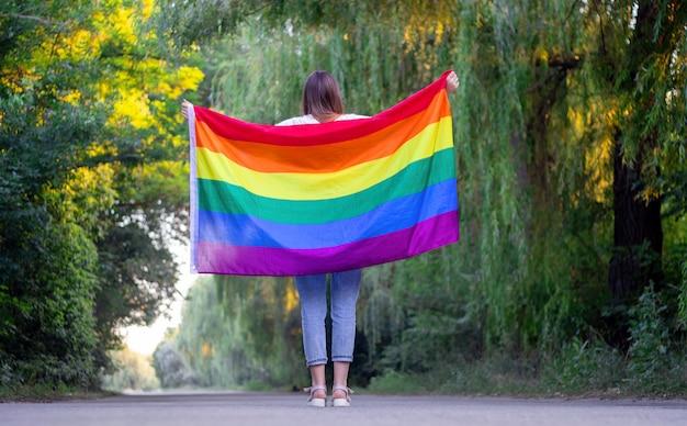 Porträt einer attraktiven frau, die eine regenbogen-lgbt-schwulenflagge auf ihren schultern hält und zur seite schaut.