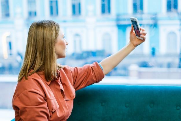 Porträt einer attraktiven, fröhlichen bloggerin, die auf der couch sitzt und selfie-freizeit in l...