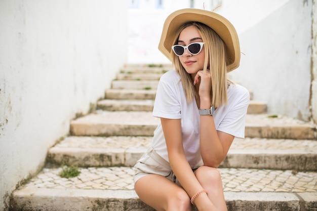 Porträt einer attraktiven glücklichen frau, die auf treppen an der stadtstraße sitzt