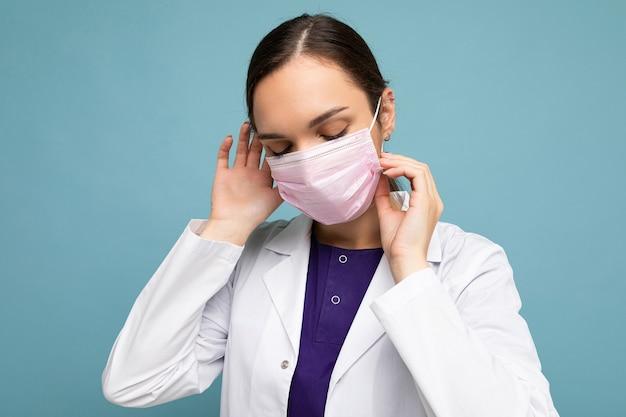 Porträt einer attraktiven jungen ärztin in weißem kittel und medizinischer maske, die isoliert auf blauem hintergrund steht