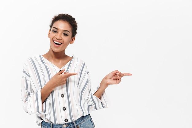 Porträt einer attraktiven jungen afrikanischen frau, die isoliert über weißer wand steht und mit dem finger auf den kopierraum zeigt