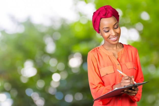 Porträt einer attraktiven jungen amerikanischen afrikanischen geschäftsfrau mit klemmbrett