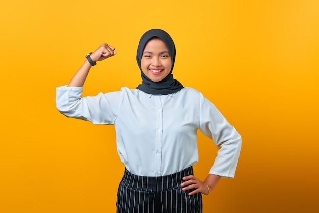 Porträt einer attraktiven jungen asiatin, die muskeln auf gelbem hintergrund zeigt