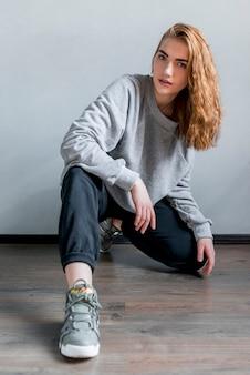 Porträt einer attraktiven jungen frau, die auf massivholzboden sich duckt