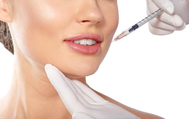 Porträt einer attraktiven jungen frau, die botox behandlung bekommt.