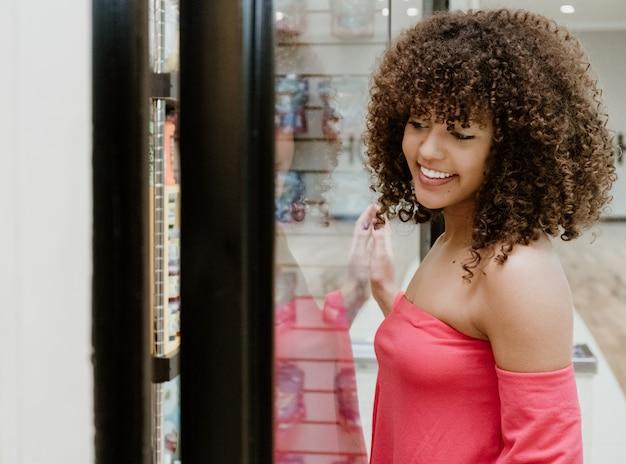 Porträt einer attraktiven jungen frau, die das shopfenster betrachtet