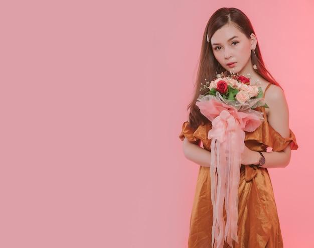 Porträt einer attraktiven jungen frau gekleidet in orange kleid, das blumenstraußblick auf kamera lokalisiert über rosa hintergrund frei von kopienraum gekleidet. asiatisches modell, das mit blumen im studio aufwirft.