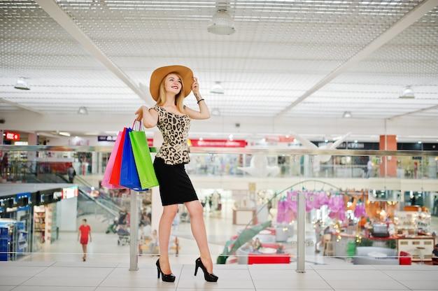 Porträt einer attraktiven jungen frau in der leopardbluse, im schwarzen rock, der mit einem hut aufwirft und in den einkaufstaschen.