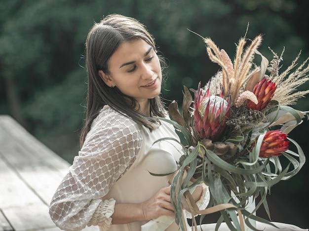 Porträt einer attraktiven jungen frau mit einem strauß exotischer blumen, ein strauß mit protea-blumen.