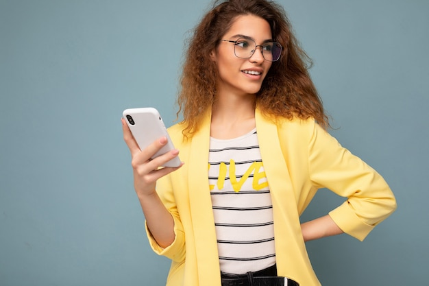Porträt einer attraktiven jungen frau mit lockigem dunkelblondem haar, die eine gelbe jacke und eine optische brille trägt, die auf dem hintergrund isoliert ist und das telefon mit blick zur seite hält