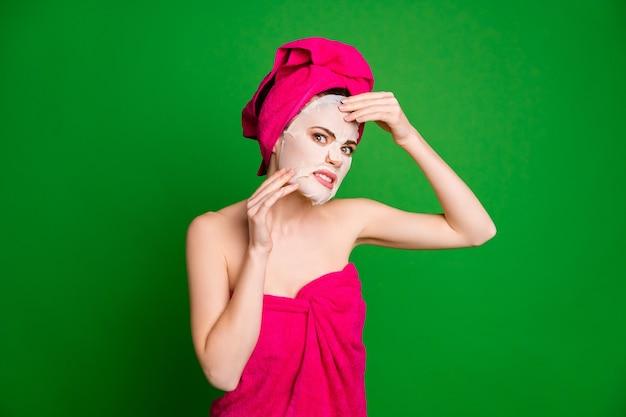 Porträt einer attraktiven nackten, gereizten dame mit turban, die gesichtsmaske verzieht, isoliert auf hellgrünem hintergrund