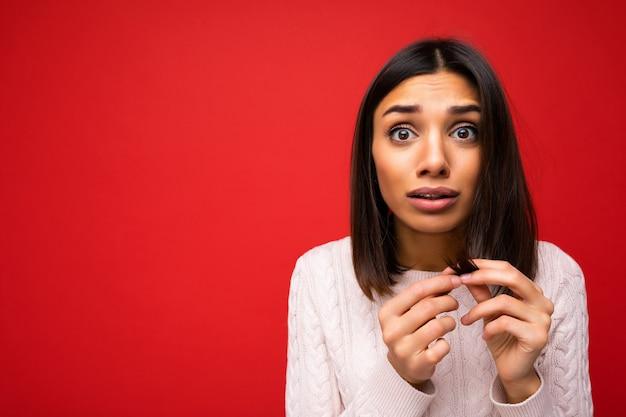 Porträt einer attraktiven, schockierten, erstaunten jungen brünetten frau, die gestricktes trikot trägt, isoliert auf rotem hintergrund mit freiem platz und kurzen haaren berührend und gespaltenen enden