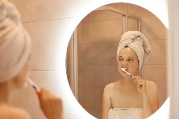 Porträt einer attraktiven schönen frau mit handtuch auf dem kopf, die vor dem spiegel im badezimmer steht und sich die zähne putzt, hygieneverfahren am morgen.