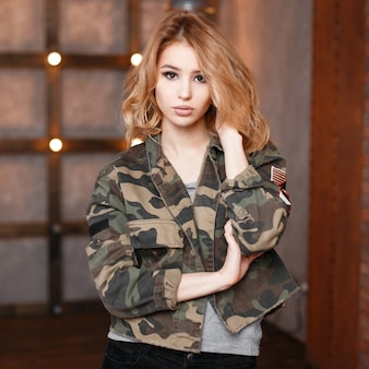 Porträt einer attraktiven sexy jungen frau mit schönen augen in einer modischen tarnjacke und grauem t-shirt im studio vor dem hintergrund einer holzwand und lichter. lockig stilvoll blond