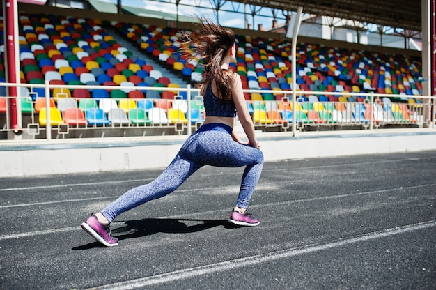Porträt einer attraktiven sitzfrau, die übungen für ihre beine im stadion tut.