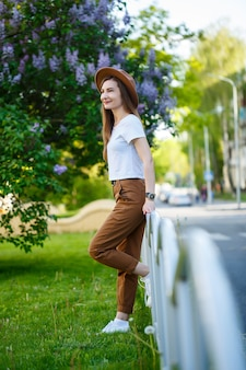 Porträt einer attraktiven, stilvollen frau mit hut mit langen blonden haaren im park, gekleidet in einem weißen t-shirt und einer braunen hose.