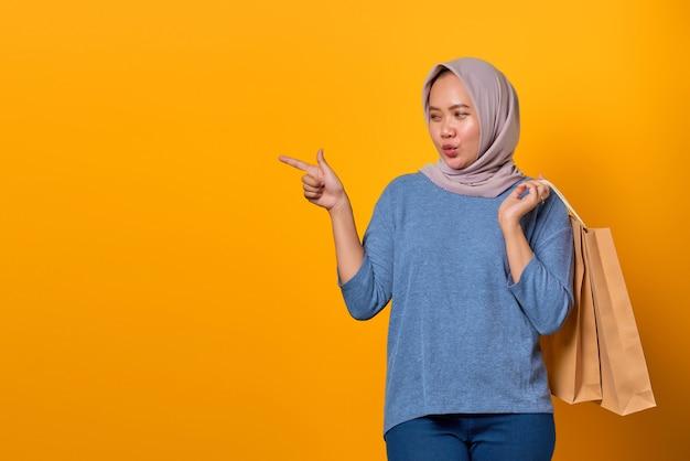 Porträt einer aufgeregten asiatischen frau, die einkaufstasche hält und mit dem finger auf den leeren raum zeigt