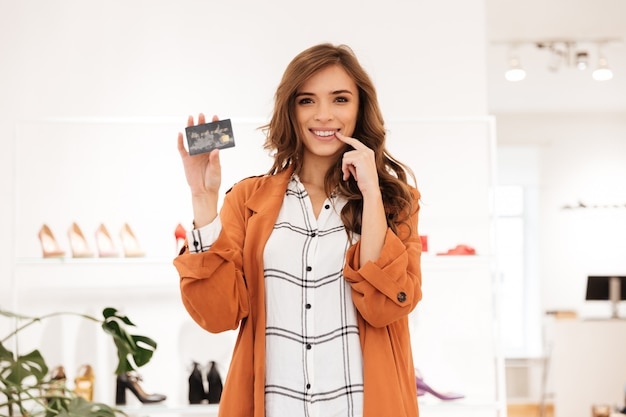 Porträt einer aufgeregten frau, die kreditkarte hält