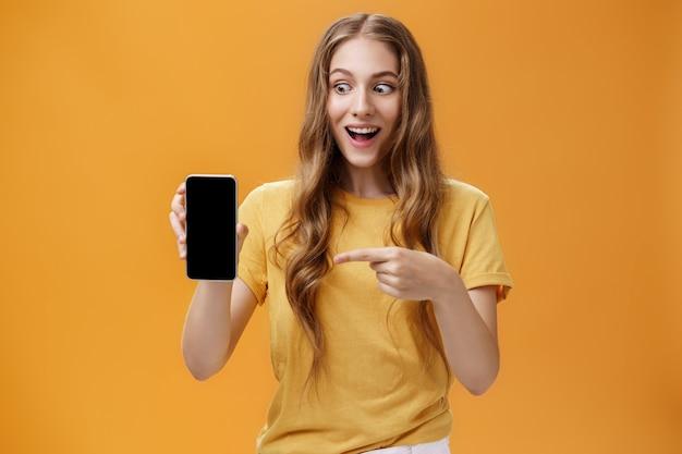 Porträt einer aufgeregten frau, die sich erstaunt fühlt, ein tolles neues smartphone in der hand zu halten und auf den handy-bildschirm zu zeigen, der wie verrückt auf das gerät knallt, das von einem coolen technologieprodukt bezaubert wird.