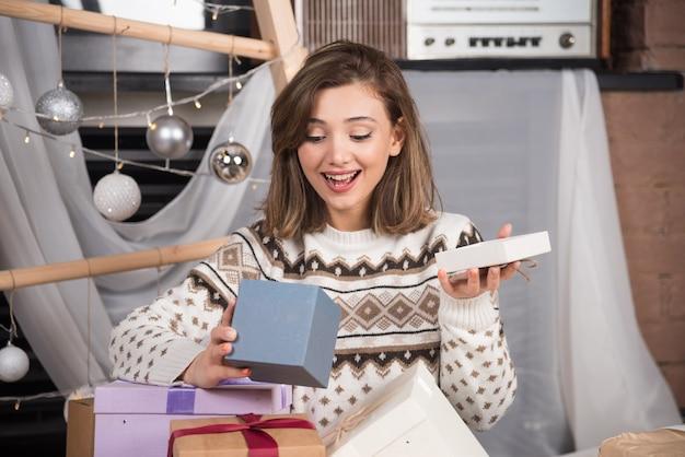 Porträt einer aufgeregten frau, die weihnachtsgeschenk öffnet.