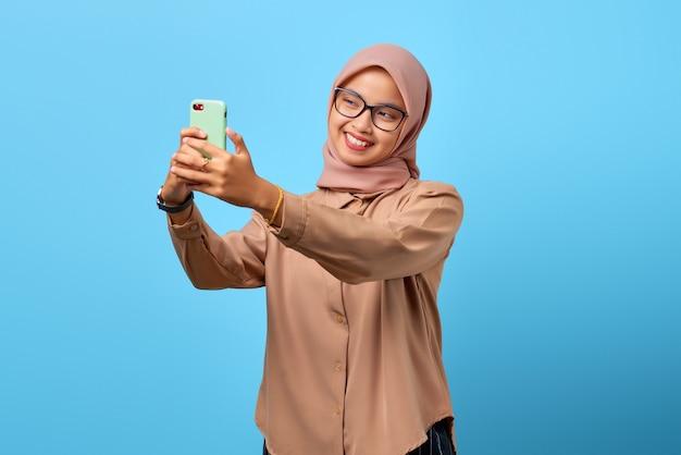 Porträt einer aufgeregten, fröhlichen jungen asiatin, die handy benutzt, macht selfie über blauem hintergrund