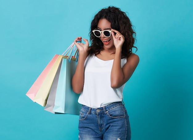 Porträt einer aufgeregten jungen hand der schwarzen frau, die einkaufstasche und sonnenbrille hält