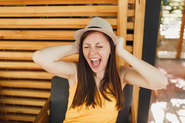 Porträt einer aufgeregten lächelnden jungen frau in strohsommerhut, gelbes hemd legte die hände auf den kopf auf der holzwand im sommercafé-café der straße im freien