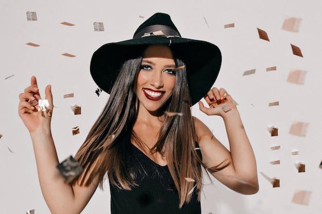 Porträt einer aufgeregten tanzenden glücklichen frau im halloween-kostüm, das über fledermäusen und konfetti-wand aufwirft. halloween-party, wahre glückliche gefühle