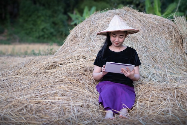 Porträt einer bäuerin, die ein digitales tablet verwendet, während sie auf einem reisfeld am strohhintergrund sitzt