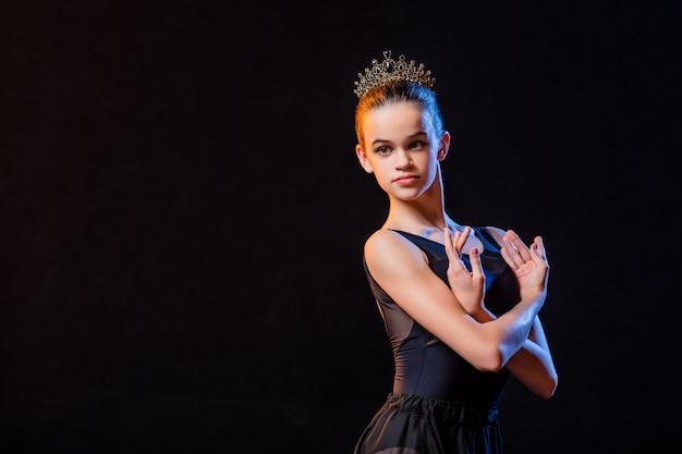 Porträt einer ballerina in einem schwarzen kleid und einer krone