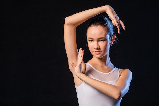 Porträt einer ballerina in einem weißen kleid an einer schwarzen wand, beleuchtet von bunten strahlen von scheinwerfern