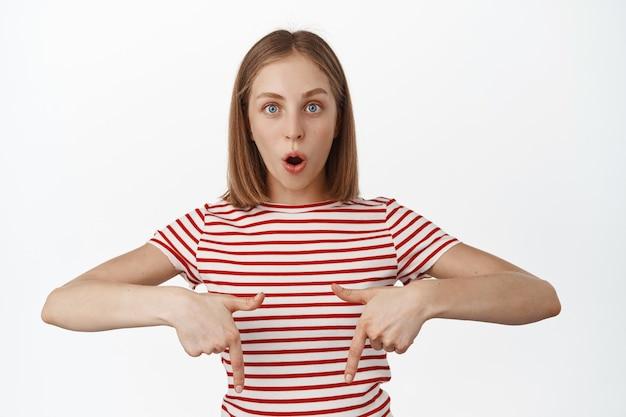 Porträt einer beeindruckten blonden frau, die kiefer fallen lässt, sagen wow, mit den fingern nach unten zeigen und erstaunt auf die vorderseite starren, das brandneue produkt auschecken, ein gutes geschäft im geschäft zeigen, promo-angebot, weiße wand.