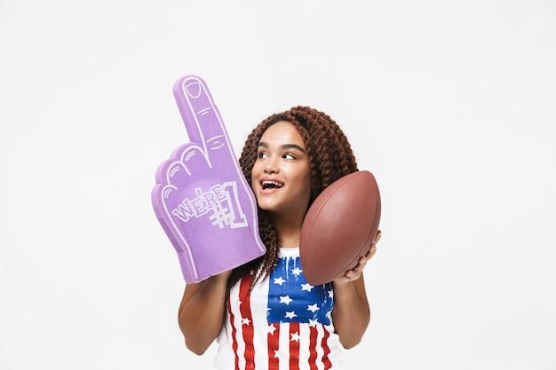 Porträt einer begeisterten frau, die den handschuh nummer eins und den rugbyball hält, während sie isoliert gegen die weiße wand steht?