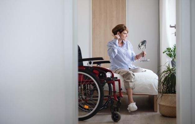 Porträt einer behinderten reifen frau, die zu hause auf dem bett sitzt