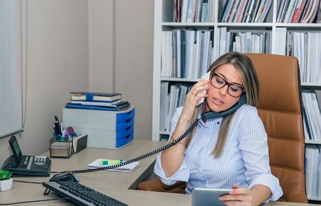 Porträt einer beschäftigten geschäftsfrau, die gleichzeitig auf handy und stationärem telefon spricht, während sie ein elektronisches tablet in ihren händen sieht