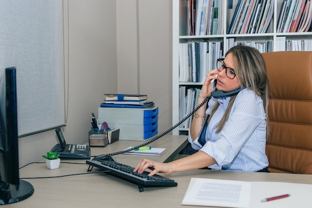 Porträt einer beschäftigten geschäftsfrau, die gleichzeitig auf handy und stationärem telefon spricht