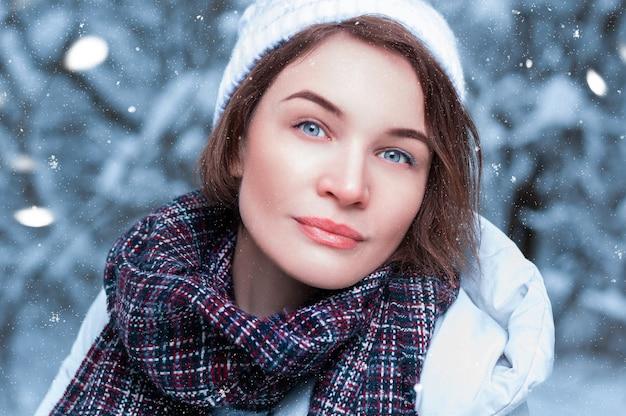 Porträt einer bezaubernden frau in der winterkleidung auf einem der schneebedeckten bäume