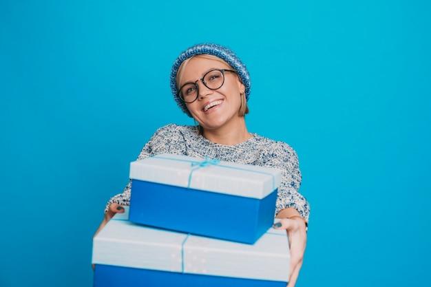 Porträt einer bezaubernden jungen kurzhaarigen frau, die junge blaue geschenkboxen lachend in blauen kleidern gegen blaue studiowand lachend gibt.