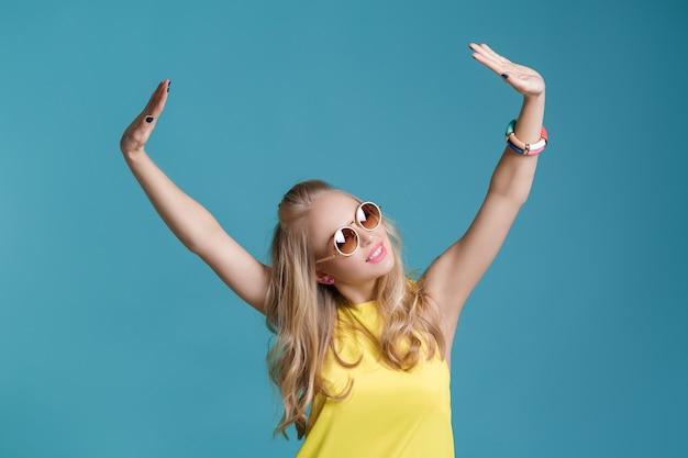 Porträt einer bezaubernden, schönen blonden frau mit sonnenbrille und gelbem hemd, die auf blauem hintergrund tanzt. unbeschwerter sommer.