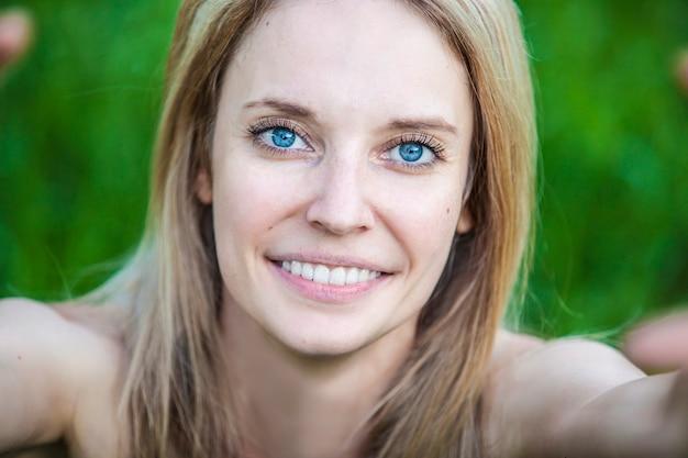Porträt einer blonden frau, die eine selbstporträt-nahaufnahme tut