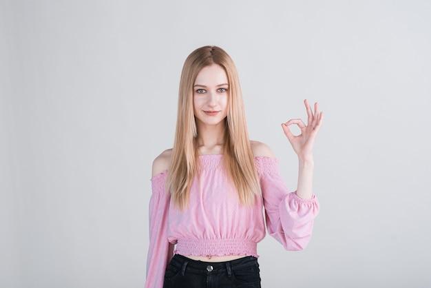 Porträt einer blonden frau, die okay-geste zeigt