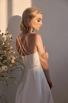 Porträt einer blonden frau in einem weißen hochzeitskleid in der abendsonne