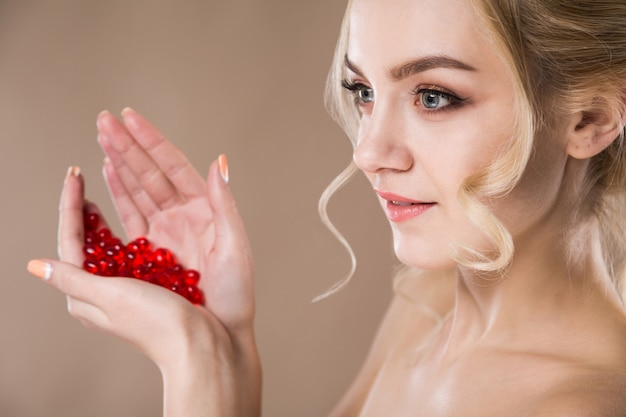 Porträt einer blonden frau mit roten kapseln von vitaminen in ihren händen