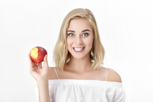 Porträt einer blonden frau mit weißen zähnen, die frische nektarine essen. weibliches lächeln