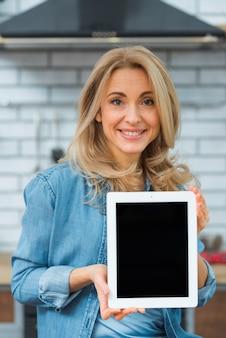 Porträt einer blonden jungen frau, die digitale tablette zeigt