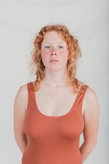 Porträt einer blonden jungen frau, die kamera gegen graue wand betrachtet