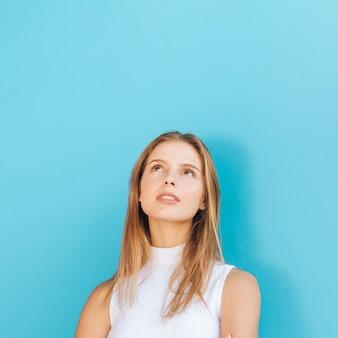 Porträt einer blonden jungen frau, die oben gegen blauen hintergrund schaut